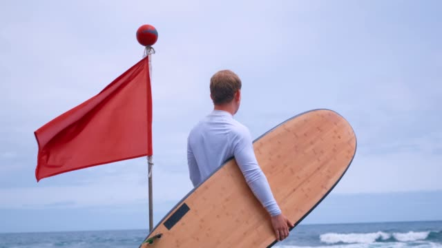 a red flag means danger and a surfer with a surfboard stands nearby and looks at the waves - spoiler filmów i materiałów b-roll