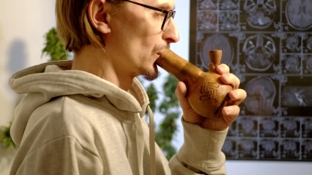 a sick Caucasian man in glasses smokes cannabis using bong against a background of a marijuana bush and an MRI image on which is his head. 4k a sick European man smokes cannabis using bong against a background of a marijuana bush and an MRI image on which his head is. 4k hashish stock videos & royalty-free footage