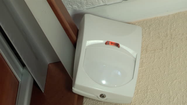 a simple white motion detector is installed in a wall corner video