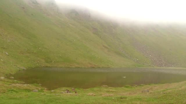 a Small Lake Located in The Valley Between The Mountains Covered in Mist video