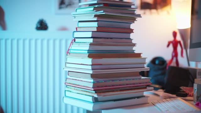 vídeos y material grabado en eventos de stock de una pila de libros se encuentra en una mesa en una oficina - imperfección