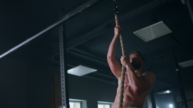 a strong pumped up man in the gym climbs the rope up and gets to the top - inerpicarsi video stock e b–roll
