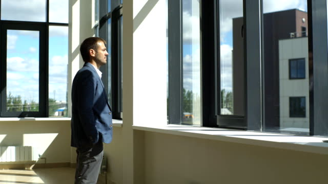 a successful businessman looks out the window and ponders the business plan video