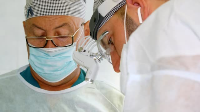 a surgeon, in medical mask and surgical loupes, and his assistant perform a surgery in hospital operating room a surgeon, in medical mask and surgical loupes, and his assistant perform a surgery in hospital operating room breast cancer awareness stock videos & royalty-free footage