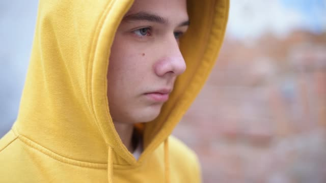 a teenager in a yellow sweatshirt looks in front of him - communication problems stock videos & royalty-free footage