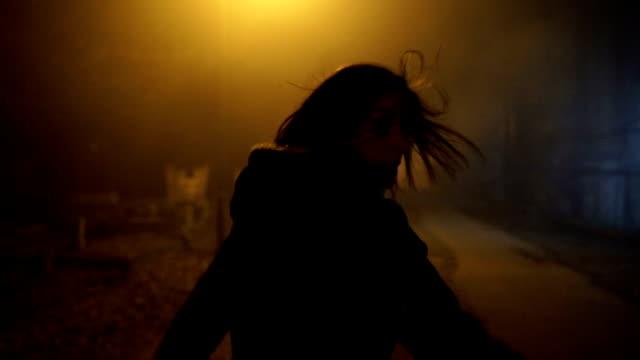 en skräckslagen kvinna springer iväg från en galning genom kyrkogården på natten - fruktan bildbanksvideor och videomaterial från bakom kulisserna
