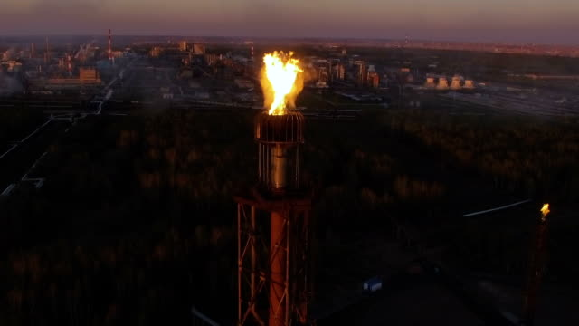 a tower with a torch on an oil refinery among the woods at sunset. Aerial view