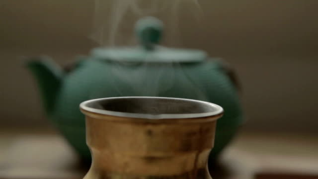 a traditional cofffee pot with steam in front of a green tea chest a traditional cofffee pot with steam in front of a green tea chest daylight savings stock videos & royalty-free footage