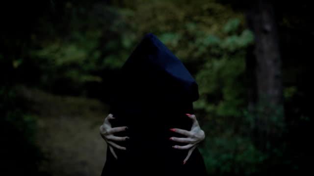 vídeos de stock, filmes e b-roll de uma mulher em um manto com capuz abraça-se atrás de suas mãos com unhas compridas, como uma bruxa, uma mulher mística caminha em linha reta através do parque - eventos de gala