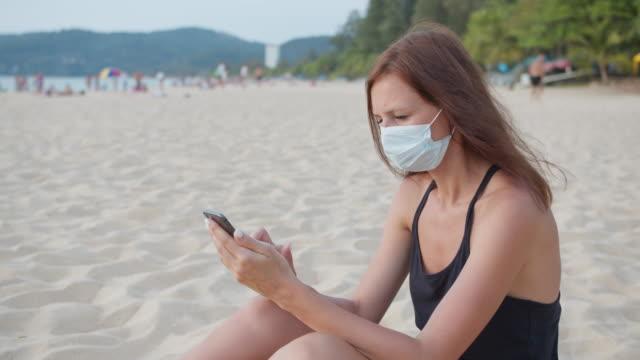 eine frau in einer medizinischen maske mit smartphone am strand - smartphone mit corona app stock-videos und b-roll-filmmaterial