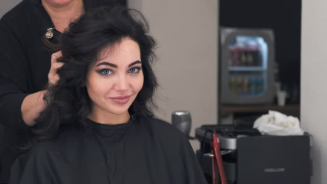 a young attractive girl is in a hair styling salon, pleased with the result, smiling at the camera. slow motion