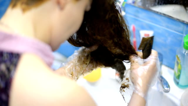 vídeos de stock e filmes b-roll de a young beautiful red-haired woman paints her hair with henna at home. organic and natural cosmetics for women. - matéria corante