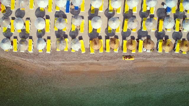 eine junge schöne frau, sonnenbaden am strand - sonnenschirm stock-videos und b-roll-filmmaterial