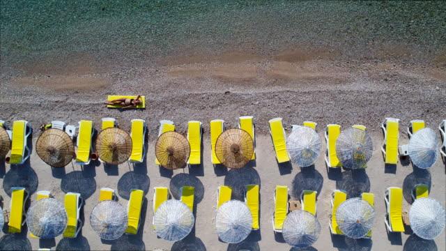 stockvideo's en b-roll-footage met een jonge mooie vrouw zonnen op het strand - gebruind