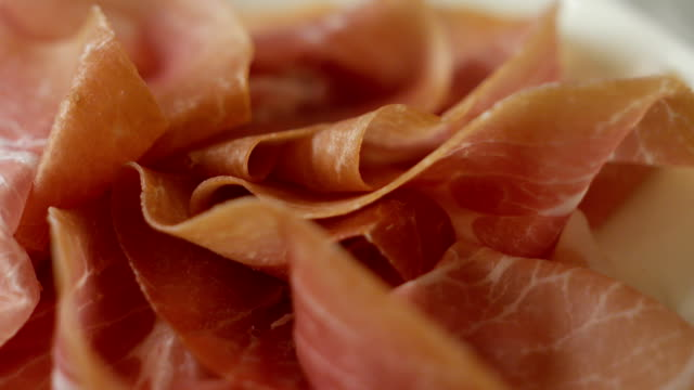 vídeos de stock e filmes b-roll de a young expert hand cuts the italian ham with a cut to the knife according to the ancient italian tradition in slow motion - presunto