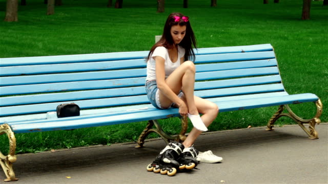 a young girl is sitting and puts on her feet rollers a young girl is sitting in a park and puts on her feet rollers charming stock videos & royalty-free footage