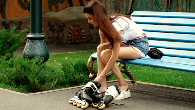 a young girl is sitting on a bench in the Park removed the rollers a young girl is sitting on a bench in the Park removed the rollers and shoes sneakers charming stock videos & royalty-free footage