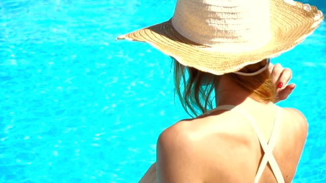 una joven vestida con un sombrero y gafas sentarse alrededor de la piscina y da vuelta a su cabeza en la cámara - vídeo