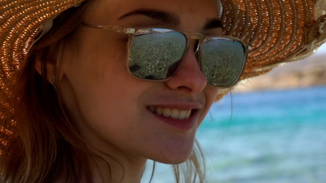 a young girl wearing a hat and glasses through which you can see the sea looks into the camera and smiling video