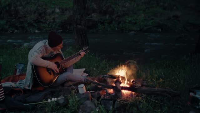 若い男が川岸の火事の前に座ってギターを弾く - キャンプ点の映像素材/bロール