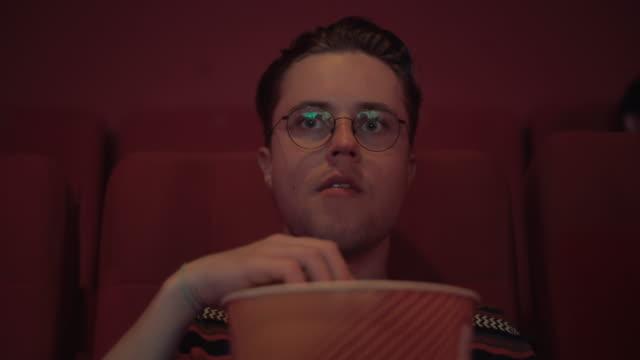 vídeos de stock, filmes e b-roll de um jovem hipster comendo pipoca enquanto assistem a estreia de um filme e uma série de televisão de uma novela - estilo de vida dos abastados