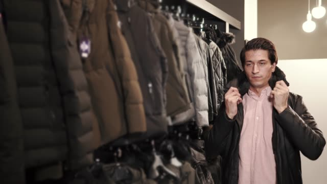 vídeos de stock e filmes b-roll de a young man chooses a jacket in a clothing store, he tries on a sample for himself - roupa quente