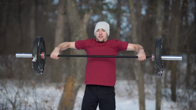 a young man is engaged in the winter time in nature, he raises a heavy barbell up, the person looks like sports enthusiastic sports video