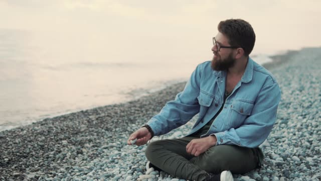 a young man sits on a rocky beach and throws pebbles into the water