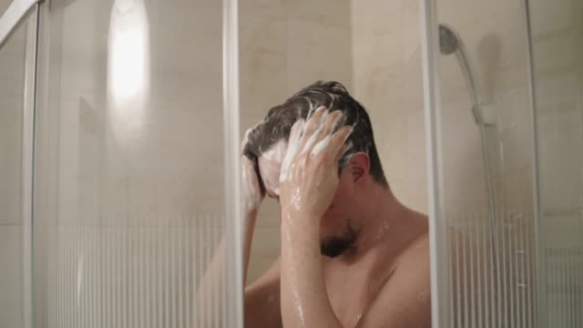 vídeos de stock e filmes b-roll de a young man thoroughly washes his head with shampoo in the bathroom - tomar banho