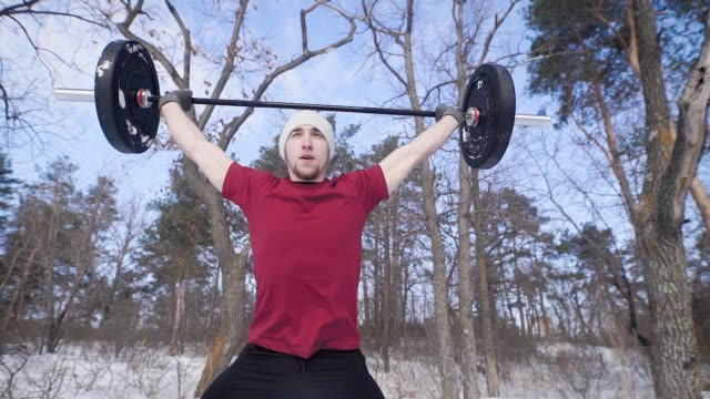 a young man who is engaged in winter time on nature crouches with a heavy barbell, the person looks sporty and healthy video