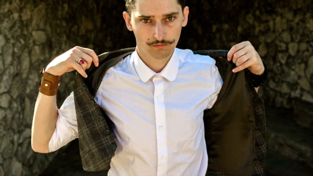 a young man with a mustache, wears a vest video