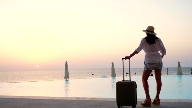 a young woman in summer clothes and sun hat, goes with a travel suitcase along the pool, at sunrise. summer. seaside resort. hot countries travel concept video