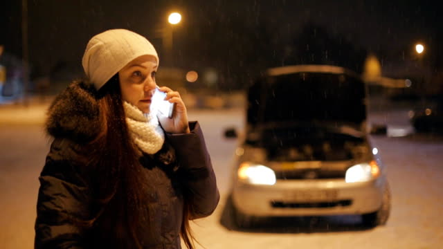 vídeos de stock e filmes b-roll de a young woman stands at night near a broken car on the road in the winter day calling on the phone, crying and swearing, asking for help. - berma da estrada