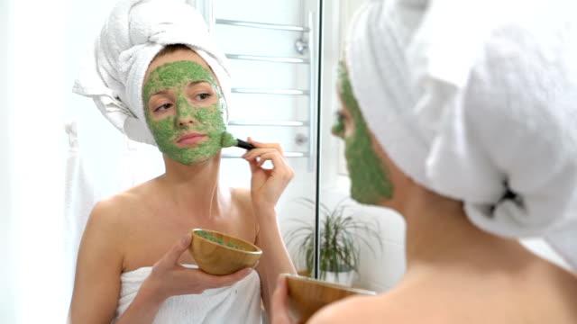 en ung kvinna med en vit handduk sätta på läpparna en grön återfuktande mask - face mask bildbanksvideor och videomaterial från bakom kulisserna