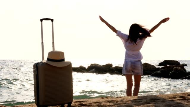 una giovane donna con le braccia tese all'alba, sulla spiaggia in fondo al mare, godendo di libertà e vita. c'è una valigia da viaggio nelle vicinanze. concetto di viaggio e benessere - dorso umano video stock e b–roll