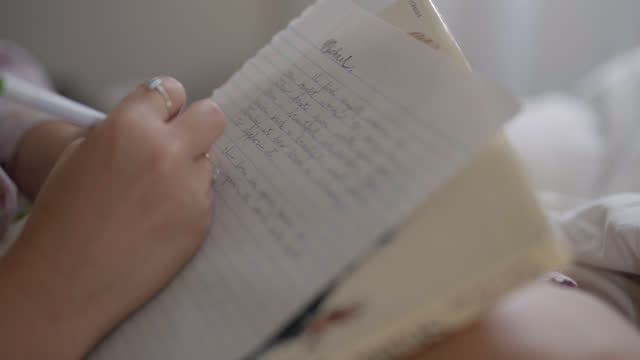 vídeos de stock, filmes e b-roll de da mão de uma jovem escrevendo uma carta de amor escrita à mão na cama - escrever