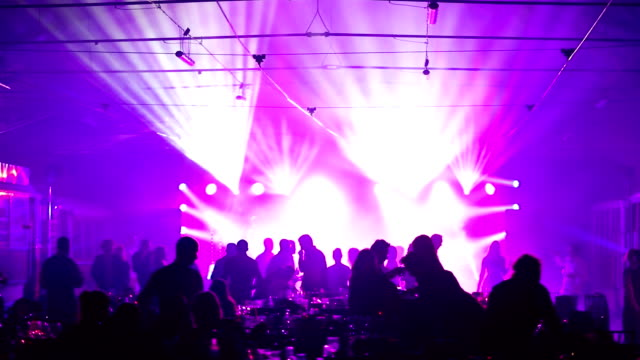 a youth party in a restaurant or a nightclub, banquet tables with alcohol and food against the background of silhouettes of dancing people, stage light and purple fill video