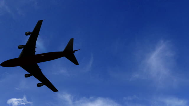 Aairplane flying overhead silhouetted plane. UHD Panning camera stock video video