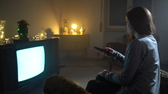 Abandoned dusk room with pile of antiques and smiling girl watching retro TV. Mistical atmosphere, warm lights in a dark room, vintage concept. Addict girl looking for entertainment channels