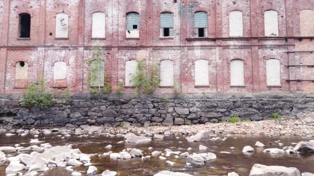 Abandoned factory on the water edge. old building on the rocky river. brown brick wall