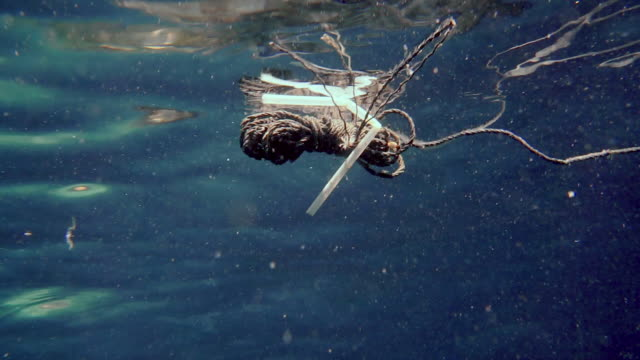abandoned fishing industry ghost net and plastic straw polluting the ocean - paglia video stock e b–roll
