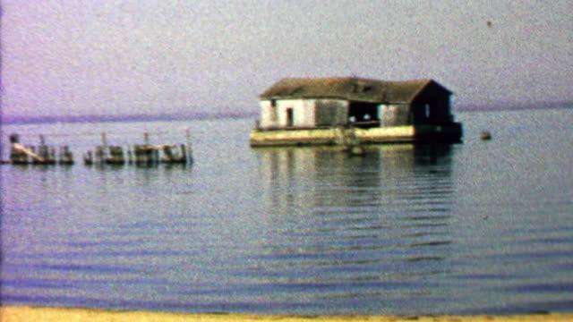 1967: Abandoned ramshackle house floating calm lake waters. video
