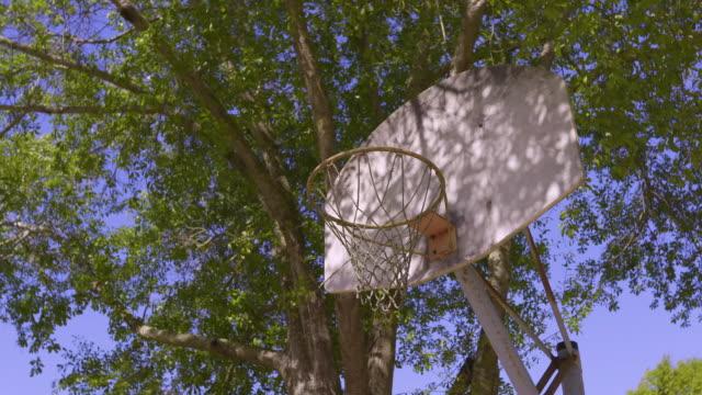 放棄された錆びたバスケットボールのフープは、住宅公園で未使用の座っています。 - 郷愁点の映像素材/bロール