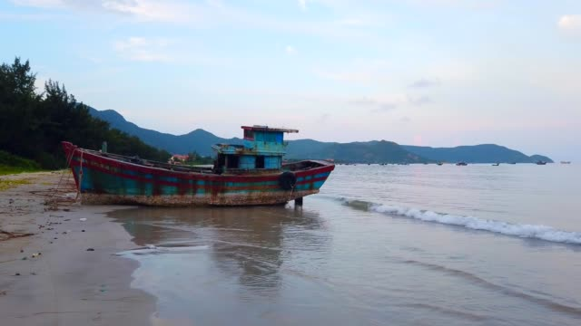 Abandoned shipwreck of wood fishing boat on beach at twilight time at Con island, Vietnam