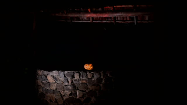 Abandoned well in the forest with Halloween pumpkin at night. Horror concept