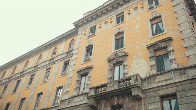 vídeos de stock, filmes e b-roll de prédio de apartamentos amarelos abandonados na itália, milão, gesso rachado nas paredes - descascado
