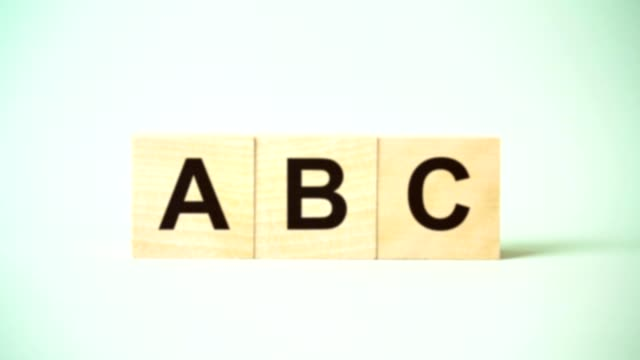 abc inscription in letters on wooden blocks isolated on blue background