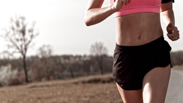 slo mo ts животе женщины бегун - спортивный бюстгальтер стоковые видео и кадры b-roll
