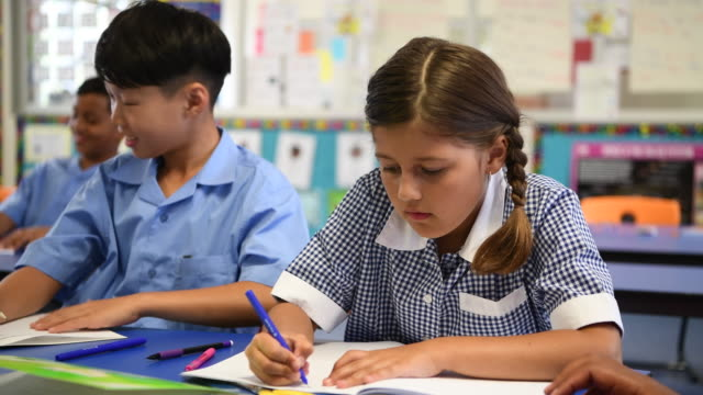 Aboriginal australian school girl wearing checked dress writing in school book at desk video