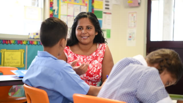 Aboriginal Australian schoolteacher smiling and helping young boy in the classroom video